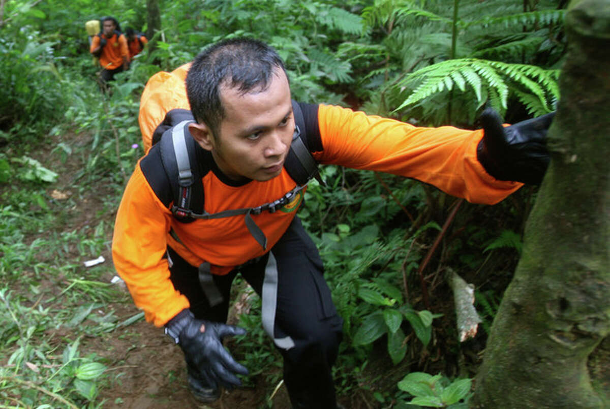 Indonesian rescuers walk through rugged terrain as they make their way to the site of a plane crash at Salak mountain in Cijeruk, Bogor, West Java, Indonesia, Thursday, May 10, 2012. Rescuers discovered the shattered wreckage of a new Russian-made passenger plane Thursday that smashed into the side of the Indonesian volcano during a flight to impress potential buyers. All on board were feared dead. (AP Photo/Achmad Ibrahim)