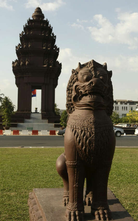 In this photo taken, Feb. 25, 2013, a lion statue sits beside the Independence Monument, in Phnom Penh, Cambodia. The Independence Monument is a striking shade of terra cotta by day and brightly illuminated by night. Glowing or not, it was constructed in 1958 to commemorate independence from the French that had been achieved five years prior. (AP Photo/Heng Sinith)