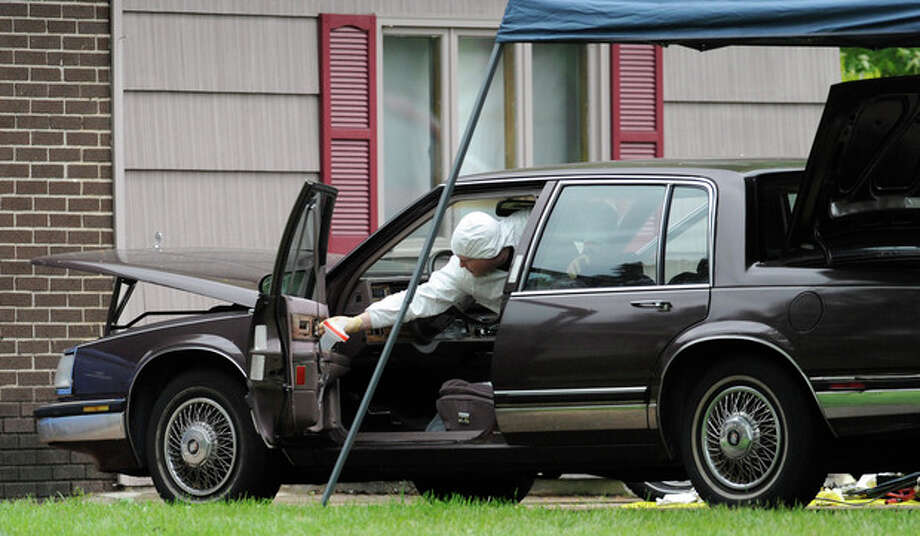 Law enforcement agents search a car at the home of reputed Connecticut mobster Robert Gentile in Manchester, Conn., Thursday, May 10, 2012. Gentile's lawyer A. Ryan McGuigan says the FBI warrant allows the use of ground-penetrating radar and believes they are looking for paintings stolen from Boston's Isabella Stewart Gardener Museum worth half a billion dollars. (AP Photo/Jessica Hill) / AP2012