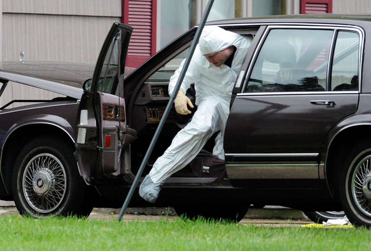 A Law enforcement agent searches a vehicle at the home of reputed Connecticut mobster Robert Gentile in Manchester, Conn., Thursday, May 10, 2012. Gentile's lawyer A. Ryan McGuigan says the FBI warrant allows the use of ground-penetrating radar and believes they are looking for paintings stolen from Boston's Isabella Stewart Gardener Museum worth half a billion dollars. (AP Photo/Jessica Hill)