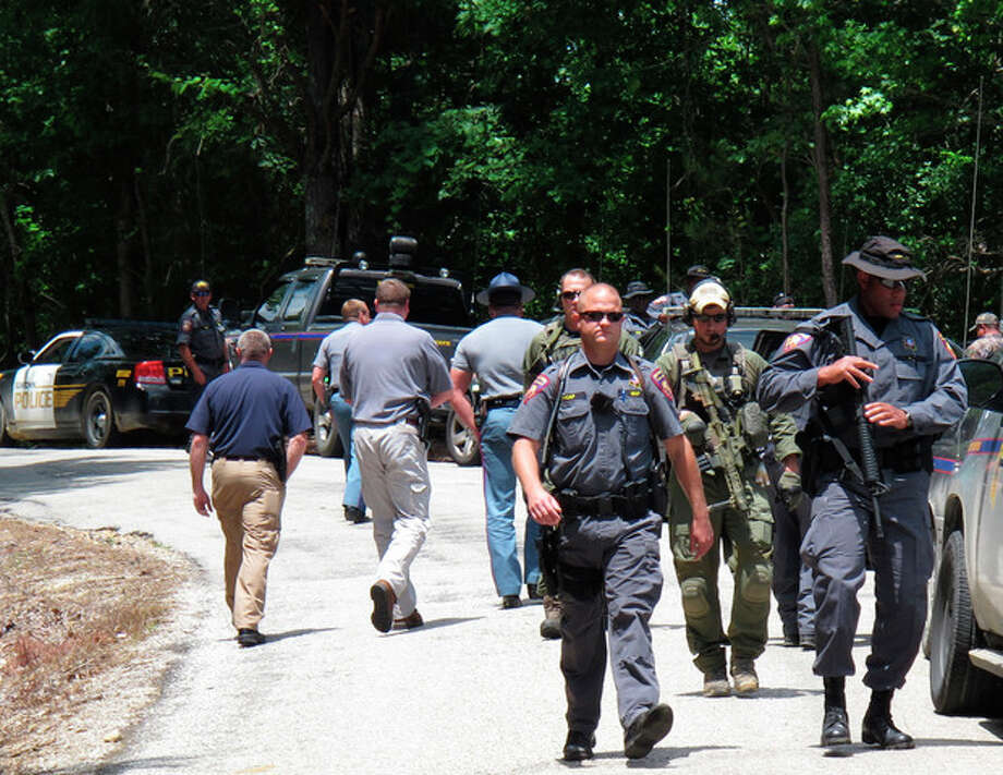 ALTERNATE CROP OF RPAS102-- FBI agents and Mississippi state troopers prepare to search for a man charged with kidnapping a Tennessee mother and her three daughters and killing two of them, Wednesday, May 9, 2012 in Guntown, Miss. The Mississippi man, Adam Mayes, 35, was added Wednesday to the FBI's 10 Most Wanted list. (AP Photo/Adrian Sainz) / Copyright 2012 The Associated Press. All rights reserved. This material may not be published, broadcast, rewritten or redistributed.