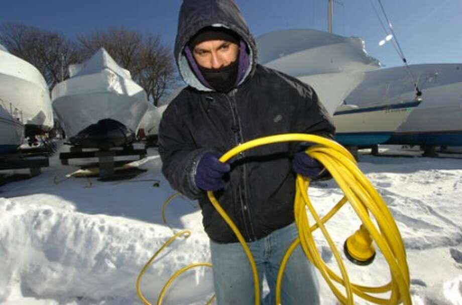 Photo/Alex von Kleydorff. Marco Vincente a Yard man with Cove Marina works at getting electrical power hooked up to a sailboat in 13 degree temps on Monday