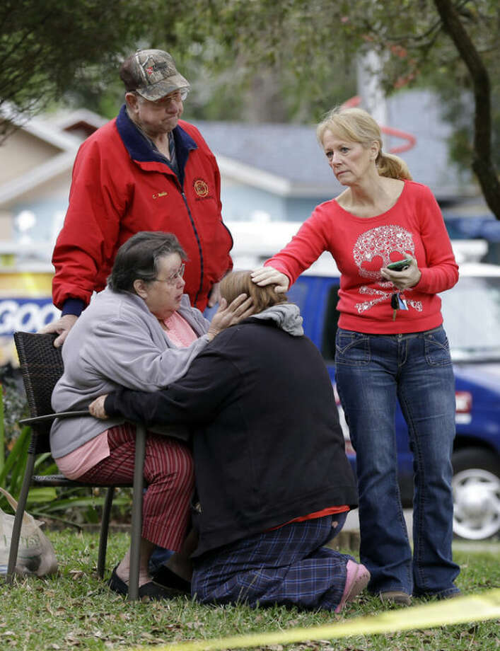 Family members console each other near the home where Jeff Bush disappeared as a large sinkhole opened under the bedroom of his house on Friday, March 1, 2013, in Seffner, Fla. Jeremy Bush told rescue crews he heard a loud crash near midnight Thursday, then heard his brother screaming. There's been no contact with Jeff Bush since then, and neighbors on both sides of the home have been evacuated. (AP Photo/Chris O'Meara)