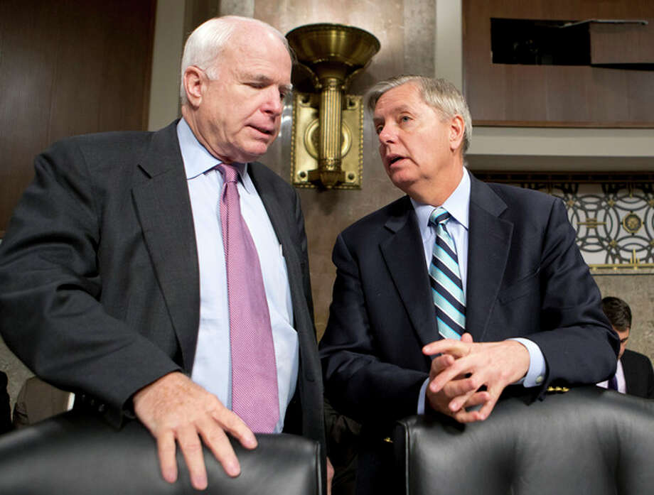 FILE - In this Feb. 14, 2013 file photo, Sen. John McCain, R-Ariz., left, and Sen. Lindsey Graham, R-S.C. confer on Capitol Hill in Washington. McCain, Sen. Lindsey Graham, R-S.C., Sen. and Jeff Flake, R-Ariz. met with key House conservatives this week to promote legislation to overhaul the nation's immigration laws and provide a pathway to citizenship for an estimated 11 million illegal immigrants, McCain's communications director said Friday. (AP Photo/J. Scott Applewhite, File) / AP