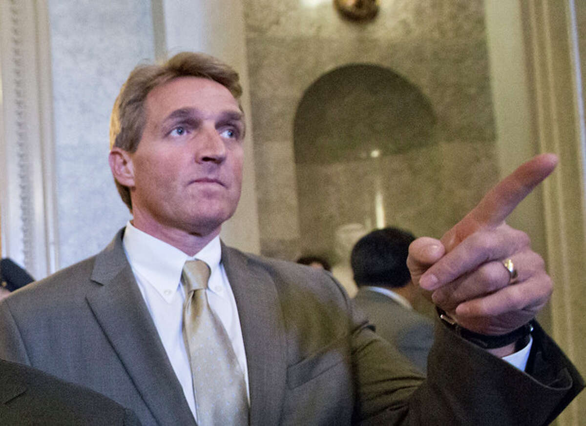 FILE - In this Feb. 28, 2013 file photo, Sen. Jeff Flake, R-Ariz. gestures as he leaves the Senate chamber on Capitol Hill in Washington. Flake, Sen. John McCain, R-Ariz. and Sen. Lindsey Graham, R-S.C. met with key House conservatives this week to promote legislation to overhaul the nation's immigration laws and provide a pathway to citizenship for an estimated 11 million illegal immigrants, McCain?'s communications director said Friday. (AP Photo/J. Scott Applewhite, File)