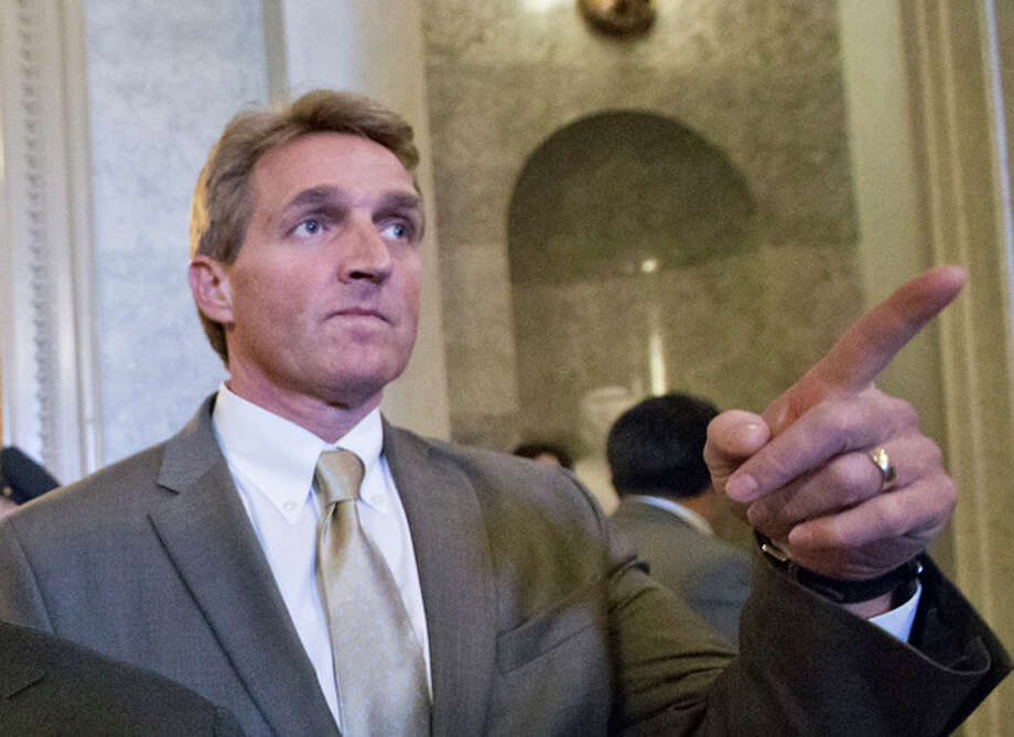 FILE - In this Feb. 28, 2013 file photo, Sen. Jeff Flake, R-Ariz. gestures as he leaves the Senate chamber on Capitol Hill in Washington. Flake, Sen. John McCain, R-Ariz. and Sen. Lindsey Graham, R-S.C. met with key House conservatives this week to promote legislation to overhaul the nation's immigration laws and provide a pathway to citizenship for an estimated 11 million illegal immigrants, McCain's communications director said Friday. (AP Photo/J. Scott Applewhite, File) / AP