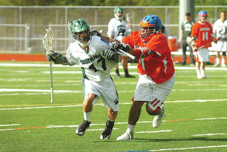 Hour photo/Alex von KleydorffNorwalk's Cameron Prescott, left, tries to make his way around a Danbury defender during Thursday afternoon's contest at Testa Field. Prescott had a pair of goals in the Bears' 12-1 victory. / 2012 The Hour Newspapers