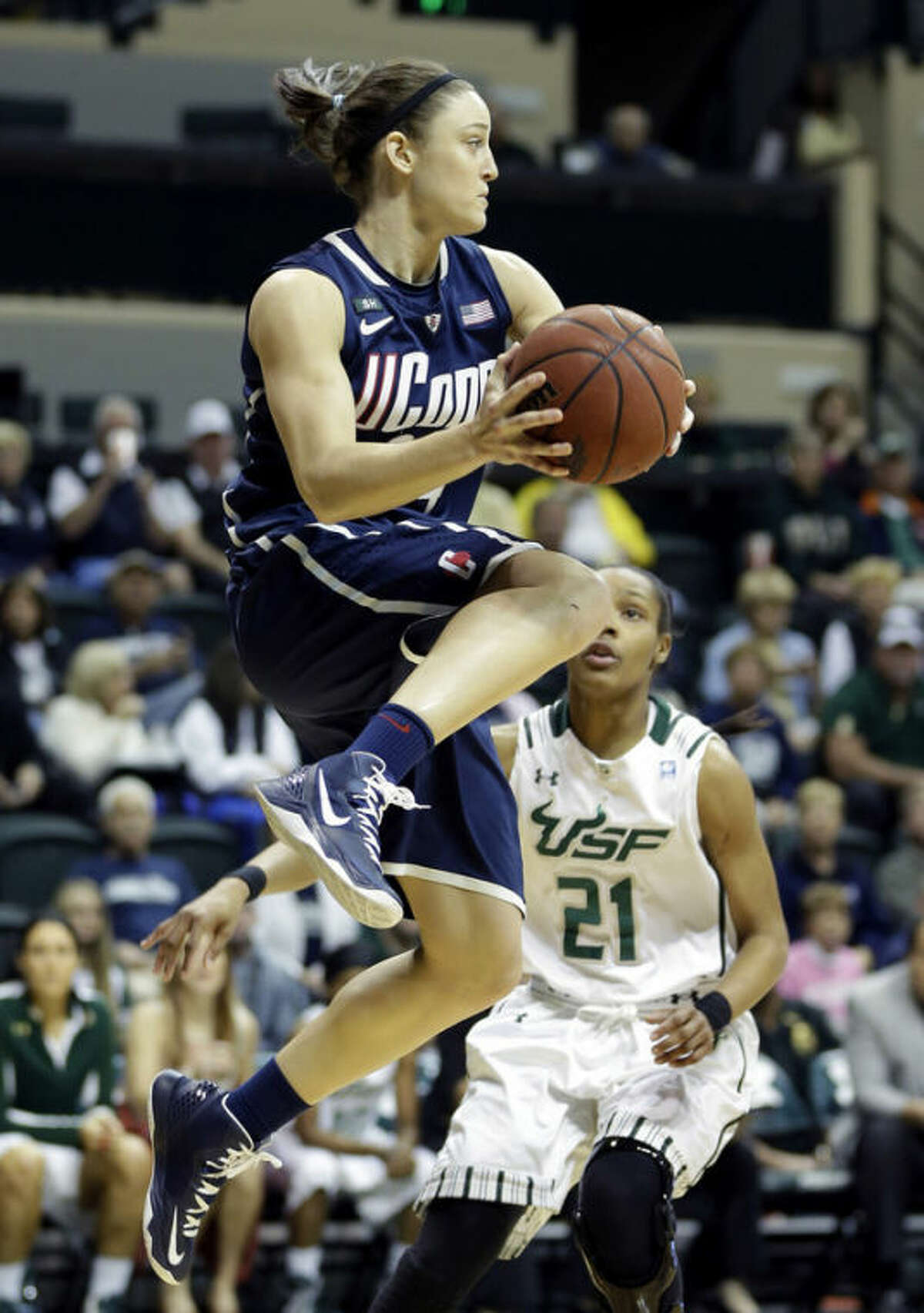 Connecticut guard Kelly Faris (34) grabs a rebound in front of South Florida guard Andrea Smith (21) during the first half of an NCAA college basketball game Saturday, March 2, 2013, in Tampa, Fla. (AP Photo/Chris O'Meara)