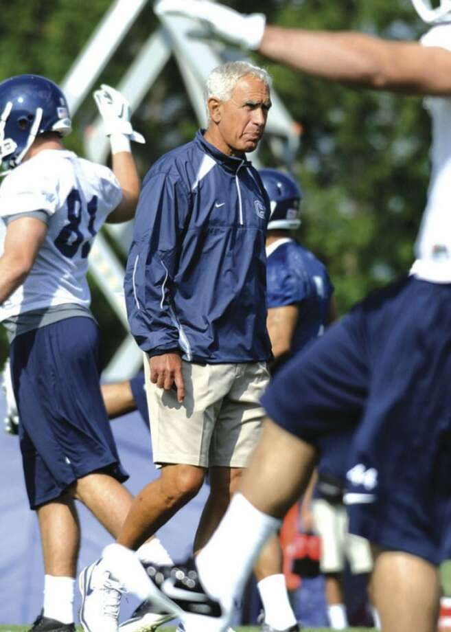 @White=[C] AP photo New UConn coach Paul Pasqualoni walks among his players during a recent practice. The Huskies not only have a new coach, but their offensive backfield is basically an all-new unit.