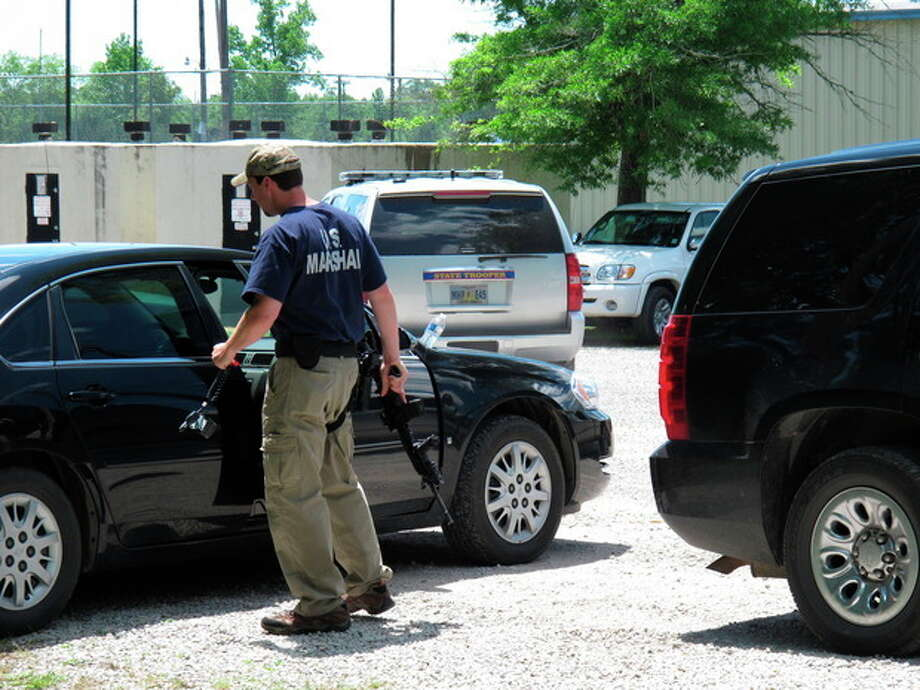 A U.S. Marshal stands next to his car holding a rifle in the parking lot of a command center set up to coordinate the search for two Tennessee girls and the man accused of abducting them and killing their mother and sister on Thursday May 10, 2012, in Guntown, Miss. The hunt for Adam Mayes and the two young sisters he is accused of kidnapping has encompassed parts of at least three counties in northern Mississippi. (AP Photo/Adrian Sainz) / AP