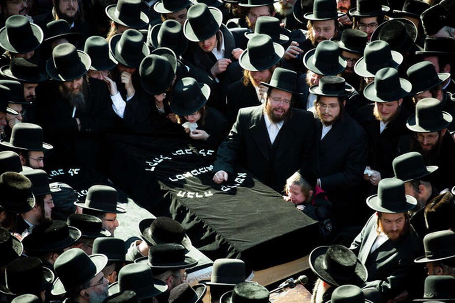 FILE - In this file photo of March 3, 2013, mourners surround a casket outside the Congregation Yetev Lev D'Satmar synagogue at the funeral for two expectant parents who were killed in a car accident early Sunday, in the Brooklyn borough of New York. The baby of Nachman and Raizy Glauber, a boy, was delivered prematurely cesarean section and survived until the next morning but died around 5:30 a.m. on Monday, March 4, 2013. Police were searching for the driver of a BMW and a passenger who fled on foot after slamming into the livery cab that transporting the 21-year-old couple to a hospital. (AP Photo/John Minchillo, File) / FR170537 AP