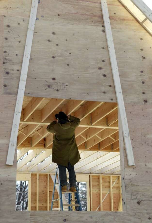 In this Feb. 13, 2012 photo, a builder works on a new single-family homw in North Andover, Mass. U.S. homebuilders are gradually growing more optimistic about the depressed housing market and believe homes sales could pick up sharply at the beginning of 2012. (AP Photo/Elise Amendola)