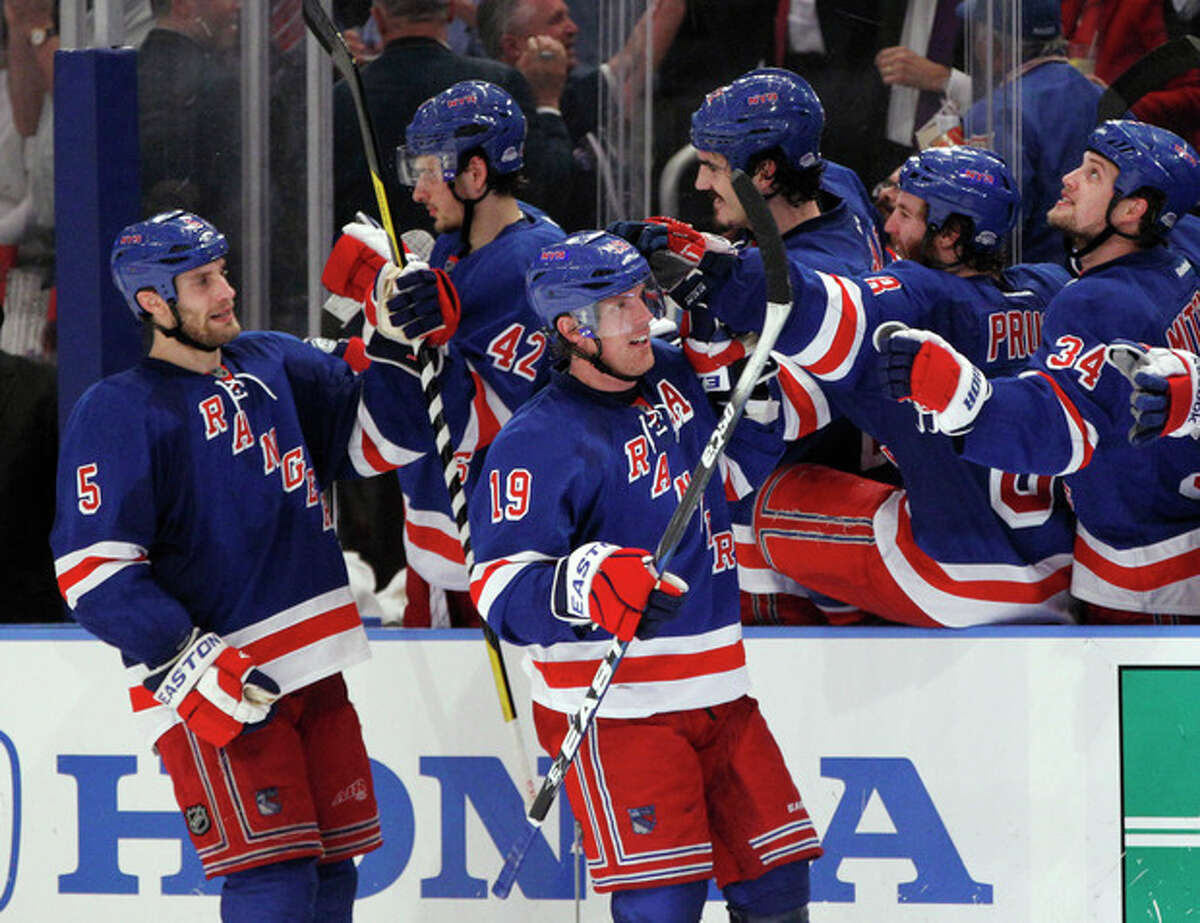 New York Rangers celebrate with Brad Richards (19) and Dan Girardi (5) after Richards scored against the Washington Capitals during the third period of Game 5 of the NHL hockey Stanley Cup Eastern Conference semifinals at Madison Square Garden in New York, Monday, May 7, 2012. (AP Photo/Kathy Willens)