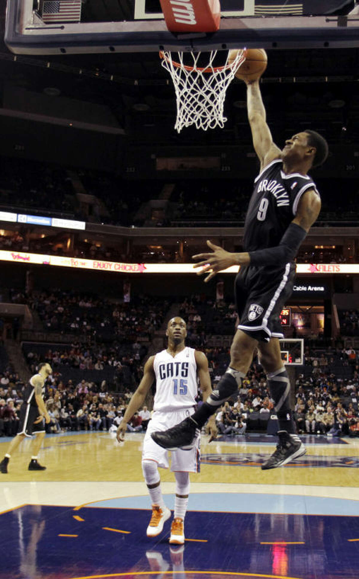 Brooklyn Nets' MarShon Brooks (9) dunks past Charlotte Bobcats' Kemba Walker (15) during the first half of an NBA basketball game in Charlotte, N.C., Wednesday, March 6, 2013. (AP Photo/Bob Leverone)
