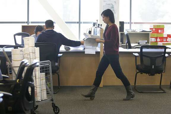 Planner technician Cindy Tong of the city's office of short term rentals registry makes copies of documents and application of a host registering their unit on Monday, June 13, 2016 in San Francisco, Calif..