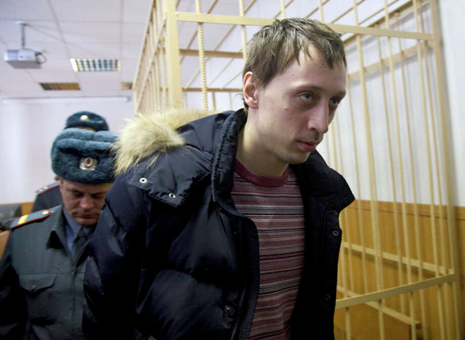 Pavel Dmitrichenko, foreground, is escorted out of a courtroom in Moscow, Russia, on Thursday, March 7, 2013. The star dancer accused of masterminding the attack on the Bolshoi ballet chief acknowledged Thursday that he gave the go-ahead for the attack, but told a Moscow court that he did not order anyone to throw acid on the artistic director's face. The judge, however, refused to release Bolshoi soloist Pavel Dmitrichenko on bail and ordered him held until at least Apr. 18 while the investigation continued. (AP Photo/Ivan Sekretarev) / AP