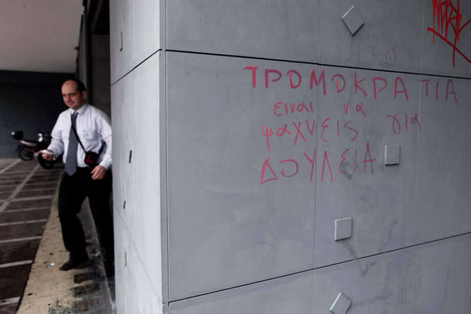 A man leaves an office of Labor Force Employment Organization (OAED) with a graffiti reading in Greek ''Terrorism = Job Seeking'' in central Athens, on Thursday, March 7, 2013. Unemployment in Greece dipped marginally to 26.4 percent in December, but experts warn that more significant improvements are unlikely in coming months. (AP Photo/Petros Giannakouris) / AP