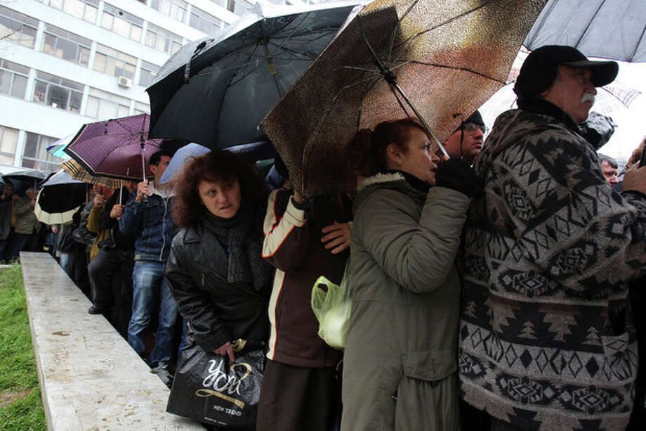 "People line up for free meat lunches under a rainfall in Athens on Thursday, March 7, 2013. It's called ""Barbecue Thursday"" _ a raucous pre-Easter celebration for meat lovers. But this year's Tsiknopempti festivities, a fixture of the Carnival season, coincided with the Greek Statistical Authority announced unemployment in Greece has dipped marginally to 26.4 percent, according to data for December. (AP Photo/Thanassis Stavrakis) / AP"