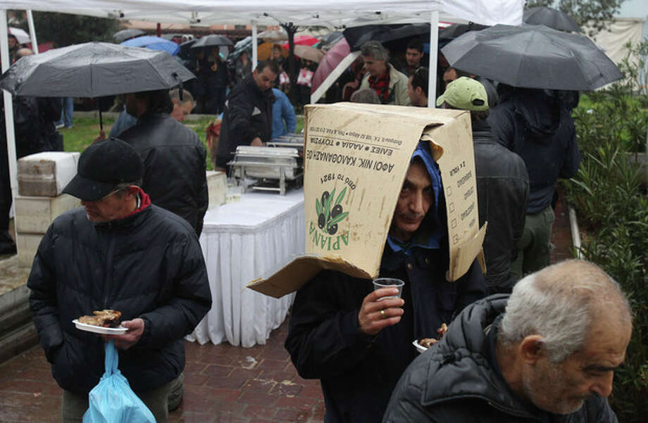 "A man uses a cardboard carton to protect himself from the rain as other people line up for free meat lunches under rainfall in Athens on Thursday, March 7, 2013. It's called ""Barbecue Thursday"" _ a raucous pre-Easter celebration for meat lovers. But this year's Tsiknopempti festivities, a fixture of the Carnival season, coincided with the Greek Statistical Authority announced unemployment in Greece has dipped marginally to 26.4 percent, according to data for December. (AP Photo/Thanassis Stavrakis) / AP"