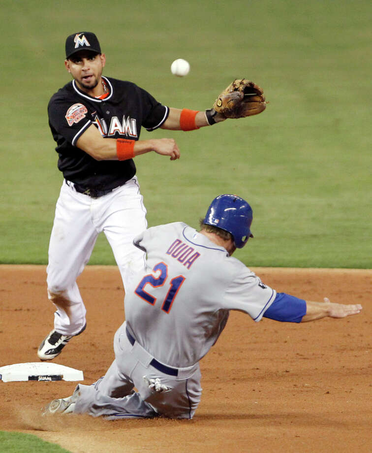 Miami Marlins second baseman Omar Infante, top, throws to first base for the double play as New York Mets' Lucas Duda (21) slides into second during the second inning of a baseball game on Friday, May 11, 2012, in Miami. Scott Hairston was out at first. (AP Photo/Wilfredo Lee) / AP