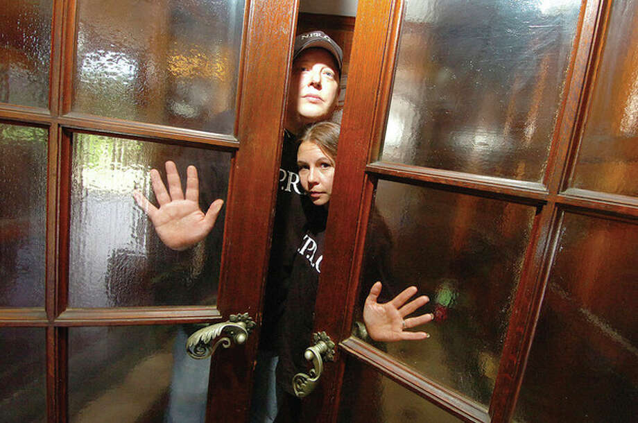 @White=[C] Hour photo / Alex von Kleydorff Todd and Lisa Harrington, with Norwalk Paranormal Research Group, stand behind a set of entryway doors at Gallaher Estate in Cranberry Park Wednesday. / 2011 The Hour Newspapers
