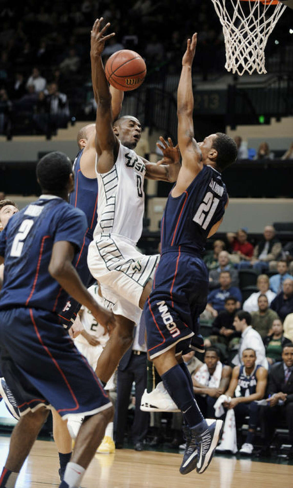 South Florida guard Martino Brock (0) loses control of the ball while attempting to a basket as Connecticut guard Omar Calhoun (21) goes up to block during the first half of an NCAA college basketball game Wednesday, March 6, 2013, in Tampa, Fla. (AP Photo/The Tampa Tribune, Chris Urso) ST. PETE, LAKELAND, BRADENTON OUT , MAGS OUT LOCAL TV OUT: WTSP CH 10, WFTS CH 28, WTVT CH 13, BAYNEWS 9