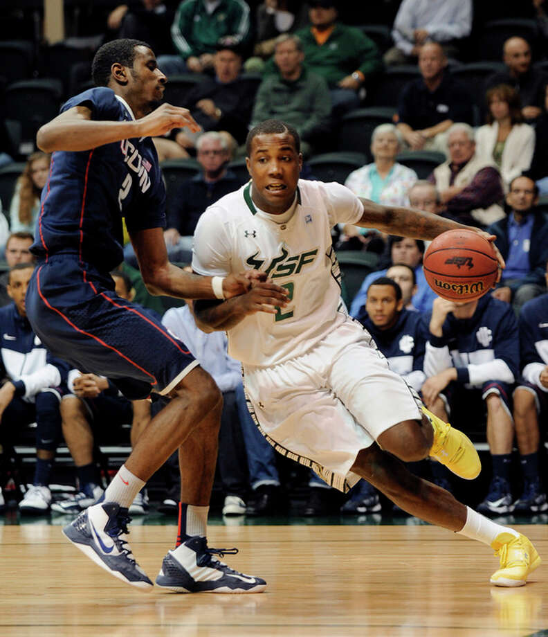South Florida forward Victor Rudd drives around Connecticut forward DeAndre Daniels (2) during the first half of an NCAA college basketball game Wednesday, March 6, 2013, in Tampa, Fla. (AP Photo/The Tampa Tribune, Chris Urso) ST. PETE, LAKELAND, BRADENTON OUT , MAGS OUT LOCAL TV OUT: WTSP CH 10, WFTS CH 28, WTVT CH 13, BAYNEWS 9 / The Tampa Tribune