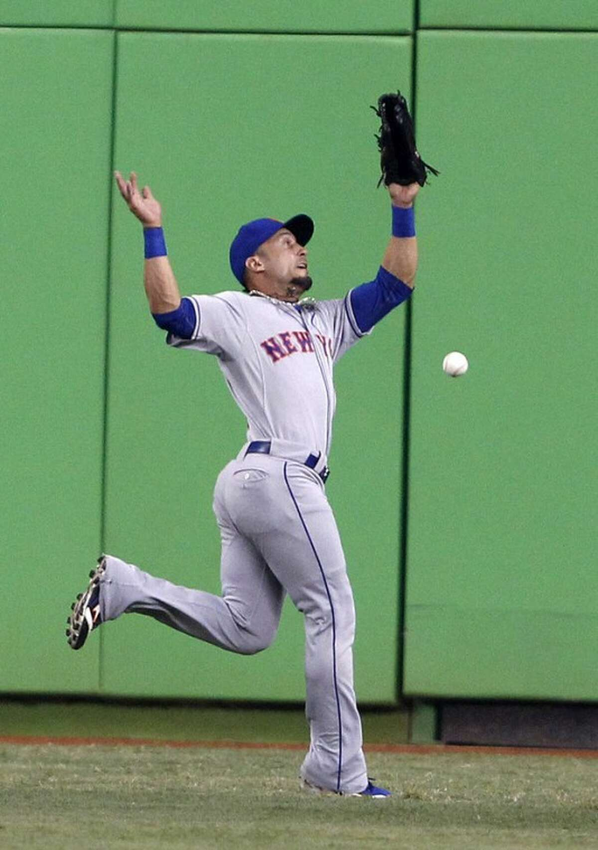 New York Mets center fielder Andres Torres is unable to catch a ball hit by Miami Marlins' Jose Reyes during the first inning of a baseball game on Friday, May 11, 2012, in Miami. Reyes had a triple on the play. (AP Photo/Wilfredo Lee)