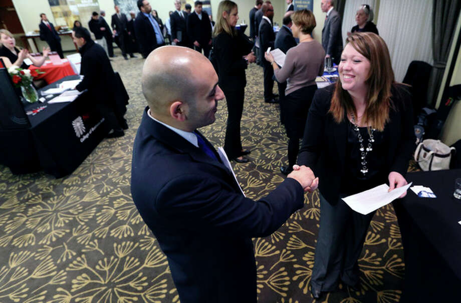 In this Monday, Feb. 25, 2013, photo, Sayed Mouawad, left, of Providence, R.I., shakes hands with Jillian Wallace of Matix, Inc., during a job fair in Boston. The number of people seeking U.S. unemployment aid fell to a seasonally adjusted 340,000 in the week ended March 2, driving down the four-week average to its lowest level in five years. (AP Photo/Michael Dwyer) / AP