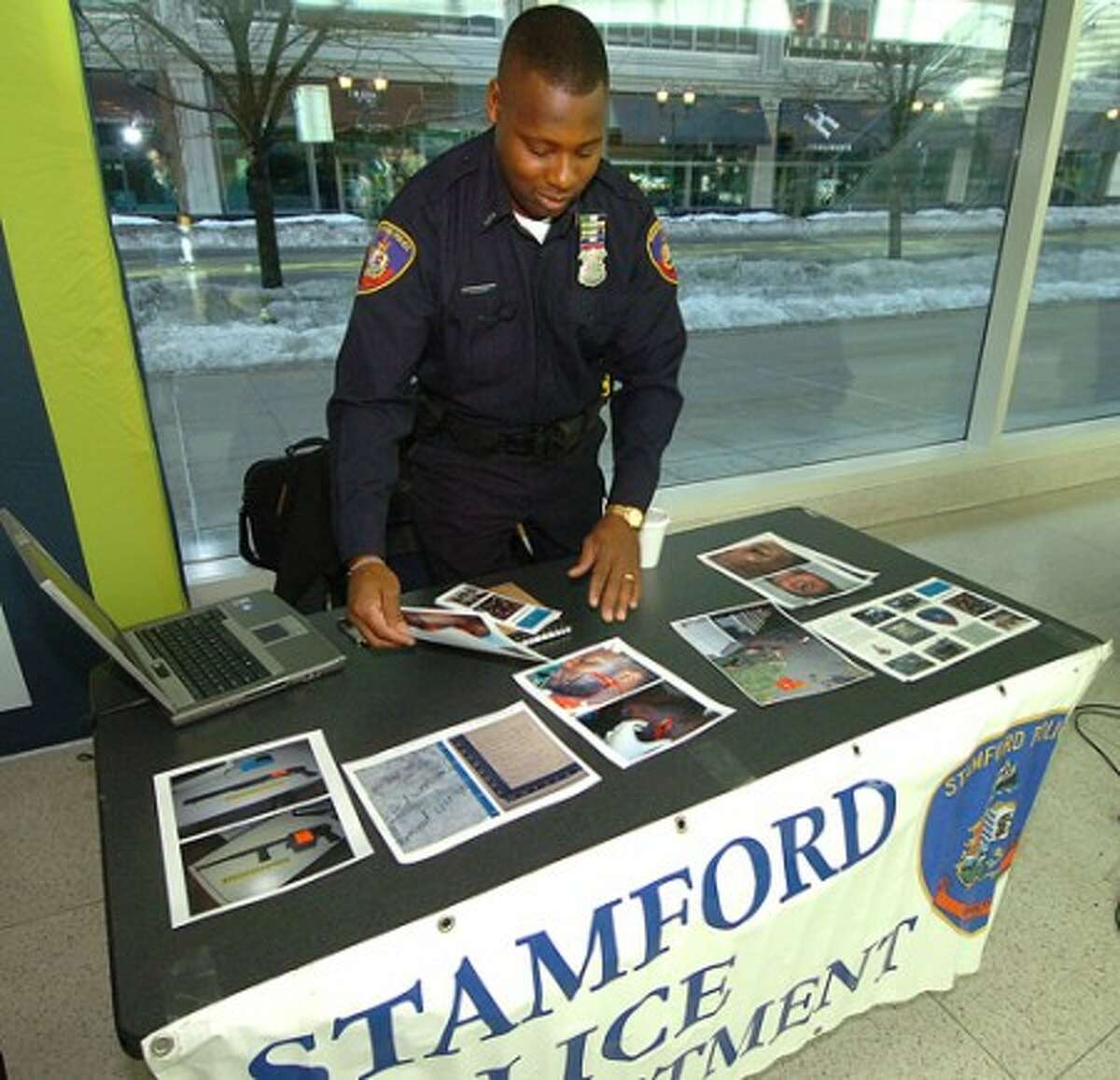 Photo/Alex von Kleydorff. Stamford Police Officer Jerry Junes sets out crime scene photos to inform the public about the life of being a police officer during UCONN''s Community Expo
