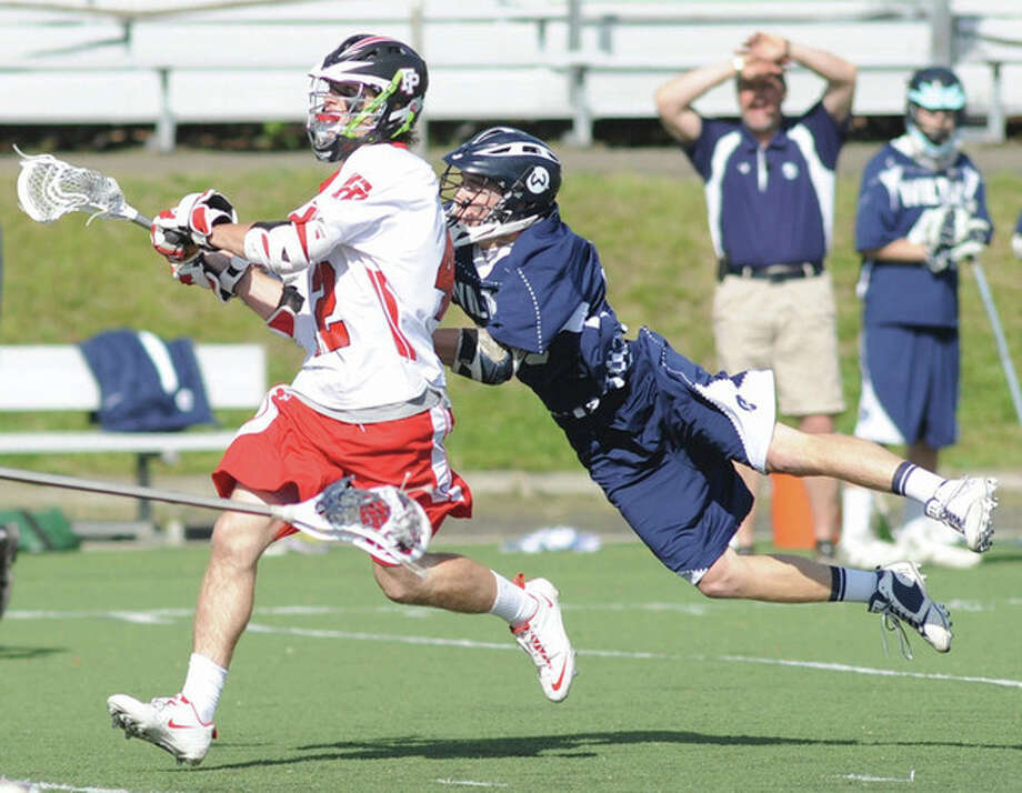 Will Kelley of Wilton, right, dives to knock the ball out of the stick of a Fairfield Prep player during Friday's game at Fairfield University.