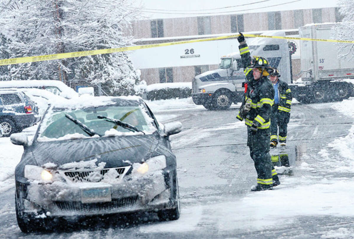 Firefighters allow traffic through Pearl St after a tractor trailer brought down sagging wires Friday morning. Snow storm Saturn which blew back over Norwalk after going out into the Atlantic left 3 inces of snow on the ground. Hour photo / Erik Trautmann