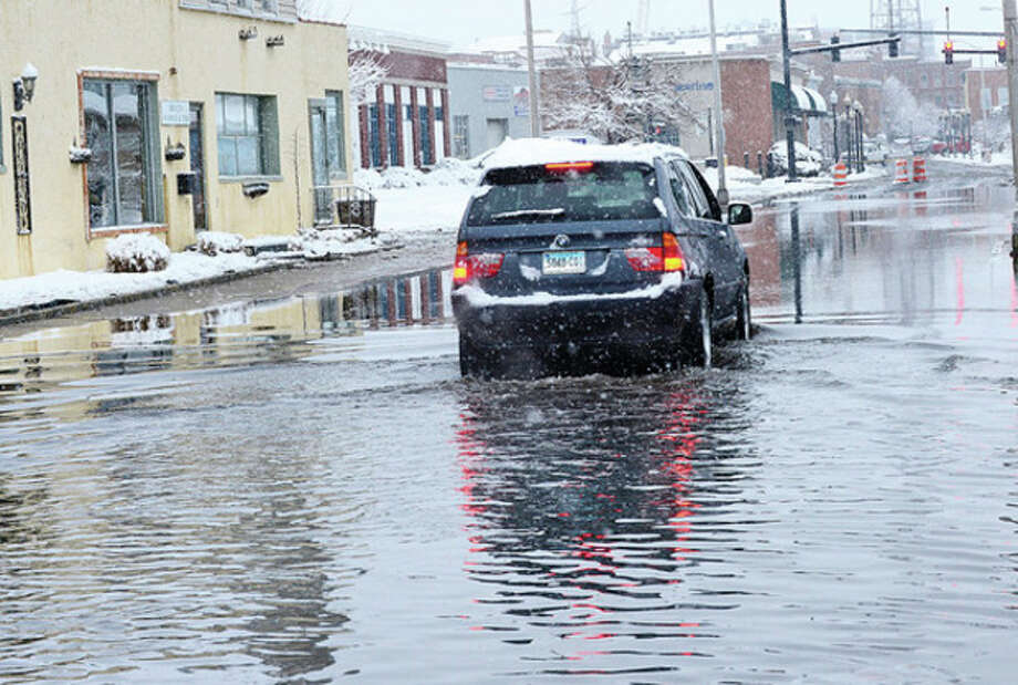 A driver braves the flooding on Water St. following snowstorm Saturn which blew back over Norwalk after going out into the Atlantic left 3 inces of snow on the ground.Hour photo / Erik Trautmann / (C)2013, The Hour Newspapers, all rights reserved