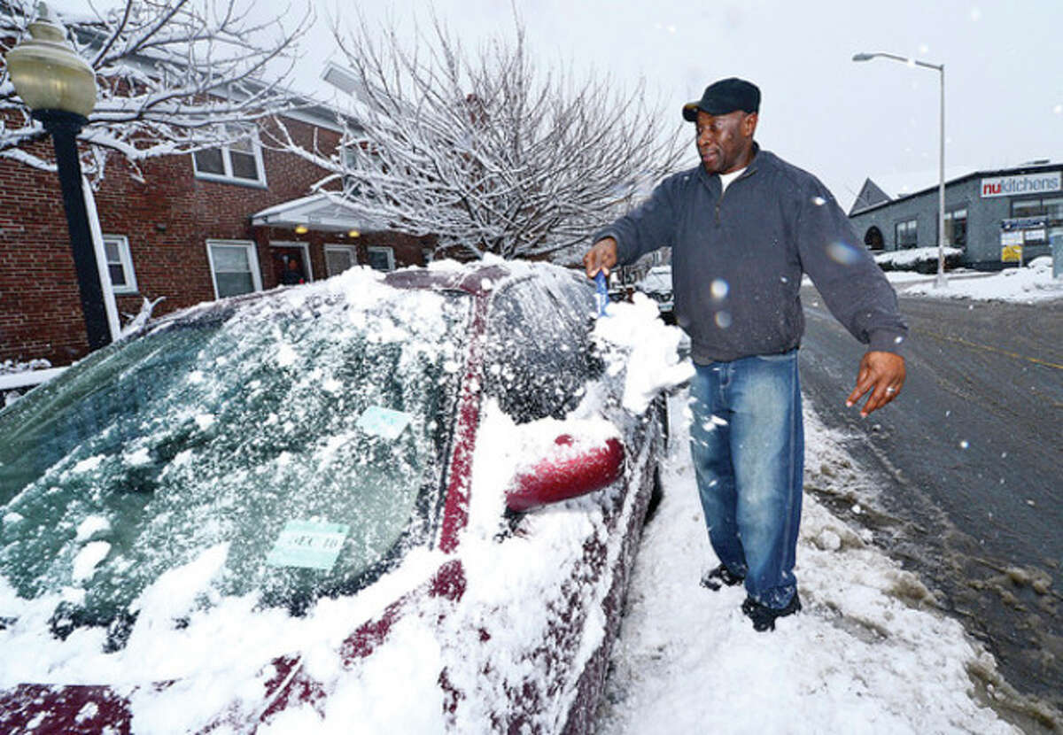 Windzer Pierre-Louis cleans off his car on Water St. following several inches of snow dumped by snow storm Saturn. Hour photo / Erik Trautmann