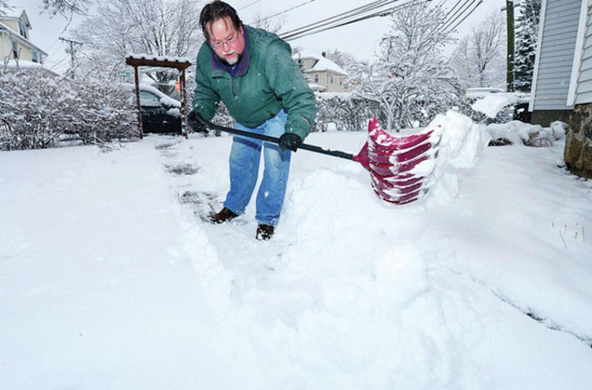 Rick Randall shovels the walk at his residence on Ward St following snow storm Saturn Friday. Hour photo / Erik Trautmann