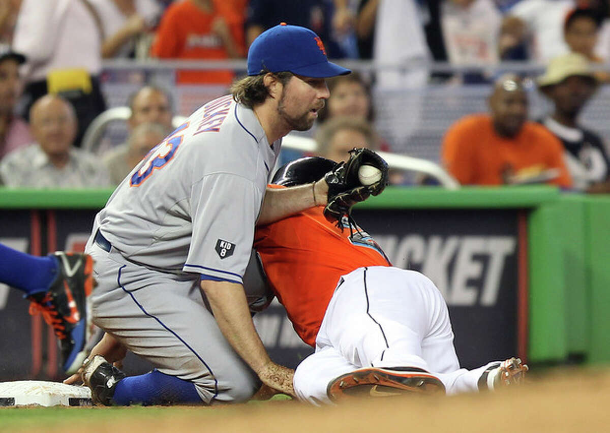 Miami Marlins' Giancario Stanton slides into New York Mets pitcher R.A. Dickey (43), who was covering third for the out during the second inning of a baseball game in Miami, Saturday, May 12, 2012. (AP Photo/J Pat Carter)