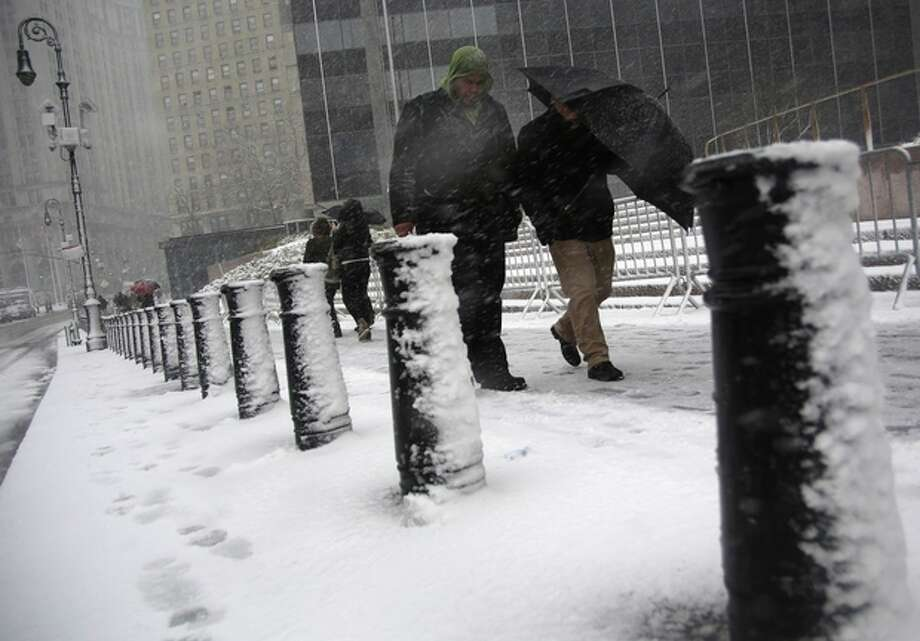 People shield themselves from driving snow in Foley Square during a storm on Friday, March. 8 2013, in New York. A very wet snow is causing slippery road conditions in the metropolitan area and several inches have fallen on eastern Long Island and Westchester, Rockland and Putnam counties.(AP Photo/Peter Morgan) / AP