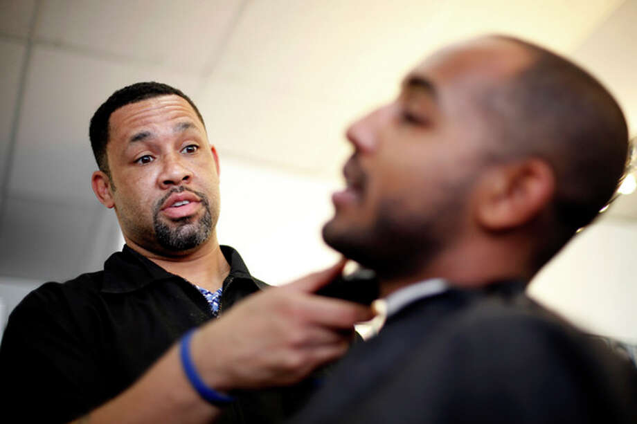 "Dorsey Jackson trims Be-Emnet Zegeye's beard at his establishment Jackson's Barbershop, Friday, May 11, 2012, in Ardmore, Pa. Like many black Americans, Dorsey Jackson does not believe in gay marriage, but he wasn't disillusioned when Barack Obama became the first president to support it. The windows of his suburban Philadelphia barbershop still display an ""Obama 2012"" placard and another that reads ""We've Got His Back."" (AP Photo/Matt Rourke) / AP"