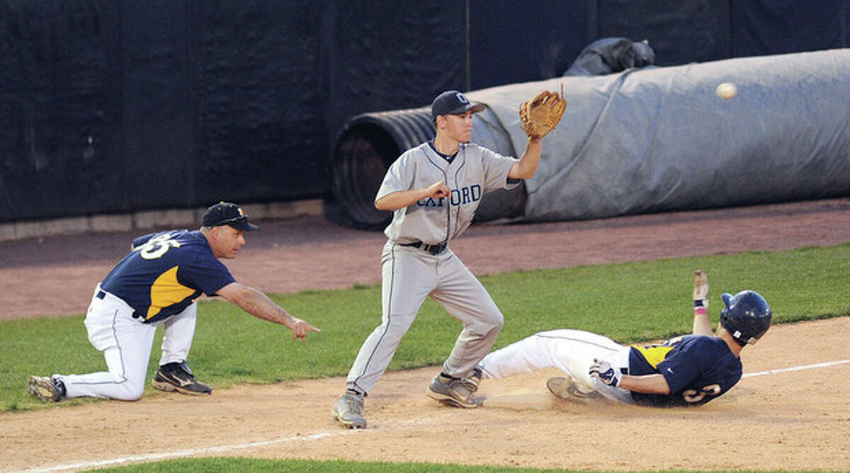 Hour photo/John Nash Weston head coach Frank Fedeli, left, points to where his Trojans baserunner Max Molinsky should slide as Oxford third baseman Dale Keller awaits the throw in the third inning of Saturday night's SWC baseball game at the Ballpark at Harbor Yard in Bridgeport.