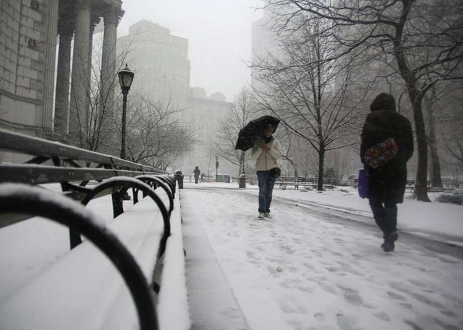 People walk through driving snow near courthouses in lower Manhattan during a storm on Friday, March. 8 2013, in New York. A very wet snow is causing slippery road conditions in the metropolitan area and several inches have fallen on eastern Long Island and Westchester, Rockland and Putnam counties.(AP Photo/Peter Morgan) / AP