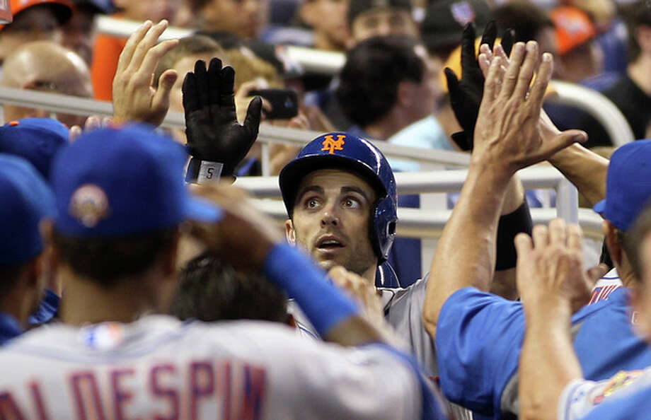 New York Mets' David Wright, center, celebrates in the dugout after hitting a third-inning home run against the Miami Marlins in a baseball game in Miami, Saturday, May 12, 2012. (AP Photo/J Pat Carter) / AP