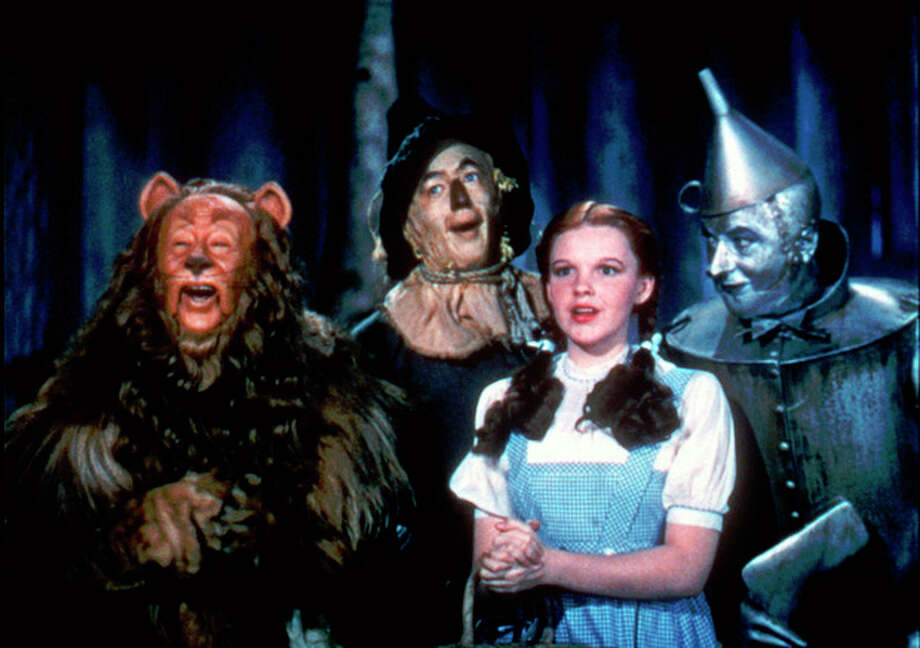 """FILE - In this undated file photo provided by Warner Bros., Bert Lahr as the Cowardly Lion, Ray Bolger as the Scarecrow, Judy Garland as Dorothy, and Jack Haley as the Tin Woodman, sing in this scene from """"The Wizard of Oz,"""" distributed by Warner Bros. On Sunday, Nov. 11, 2012, auction house Julien's Auctions said the blue pinafore dress that Garland wore in the movie fetched the highest price of any item during a two-day auction of Hollywood memorabilia that attracted bids from around the world, selling for $480,000. (AP Photo/Warner Bros., File) NO SALES / Warner Bros."""