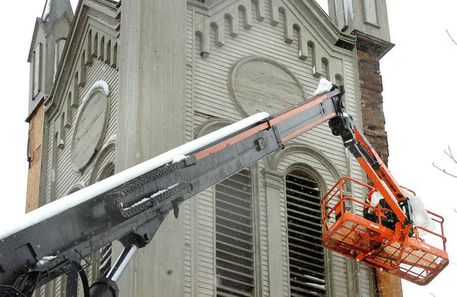 Hour Phopto/Alex von Kleydorff. Steeplejack of America carpenter Mark Buritto attaches sections of plywood on the corners of the steeple at Norwalk United Methodist Church on Friday. The Ohio based company is in the process of installing braces to secure the steeple against further deterioration until repairs of the storm damaged church can begin.