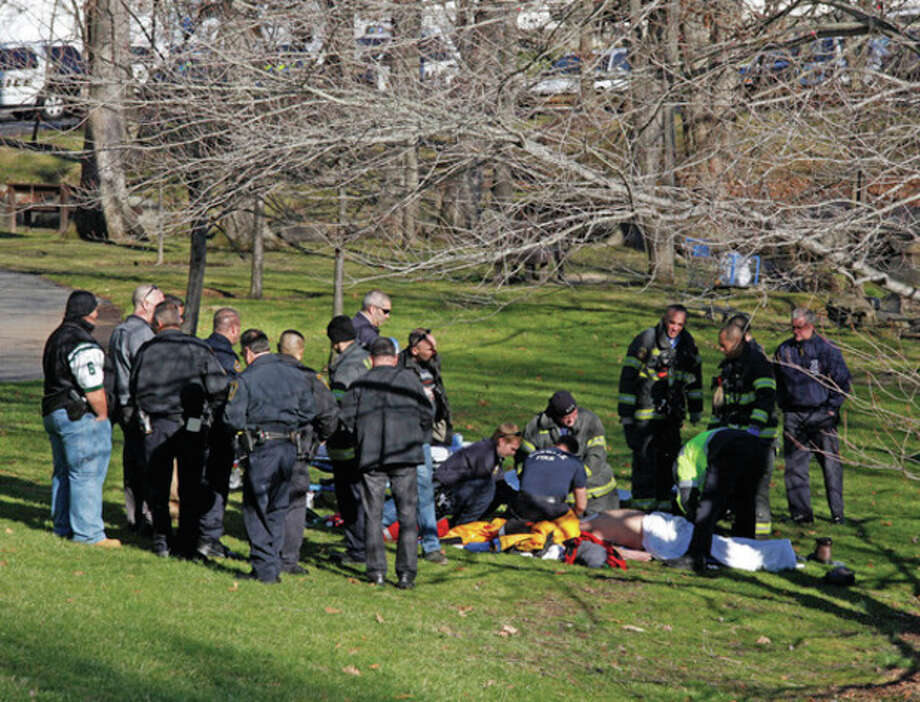 Hour photo / Danielle Robinson A rescue crew performs CPR on a body that was found in the Five Mile River Saturday afternoon near the Darien/Norwalk line on Connecticut Avenue. Below, a rescue crew wheels away