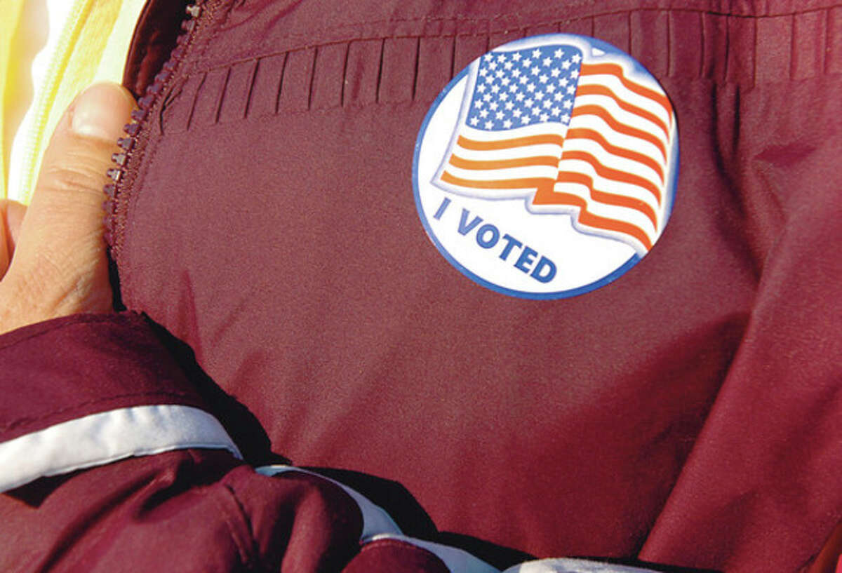 """Hour photo / Erik Trautmann A resident displays her """"I voted"""" sticker at Marvin Elementray School in Tuesday's election."""