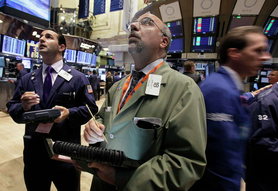 John Liotti, center, works with fellow traders on the floor of the New York Stock Exchange Monday, Oct. 24, 2011. (AP Photo/Richard Drew) / AP