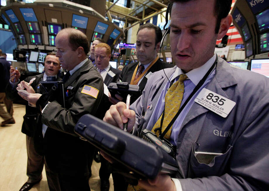 Traders gather at the post that handles HealthSpring on the floor of the New York Stock Exchange Monday, Oct. 24, 2011. HealthSpring rose 33 percent after Cigna said it will buy the health insurer for about $3.8 billion in cash.(AP Photo/Richard Drew) / AP