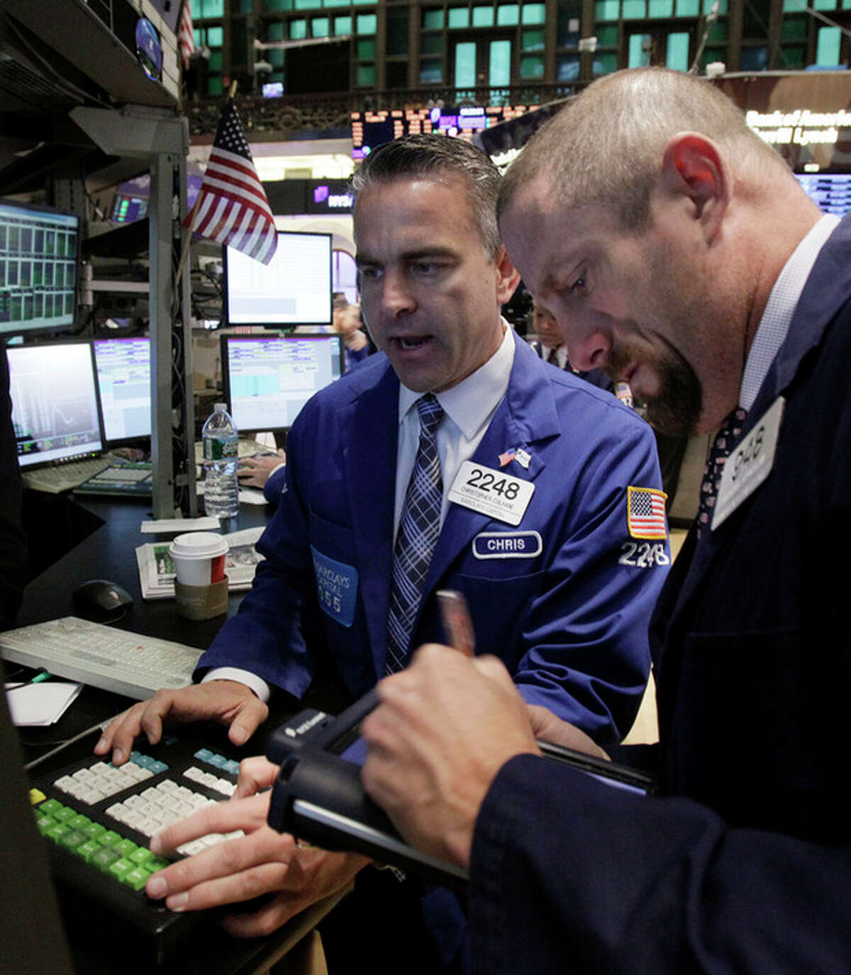 Specialist Christopher Culhane, left, works on the floor of the New York Stock Exchange Monday, Oct. 24, 2011. (AP Photo/Richard Drew)