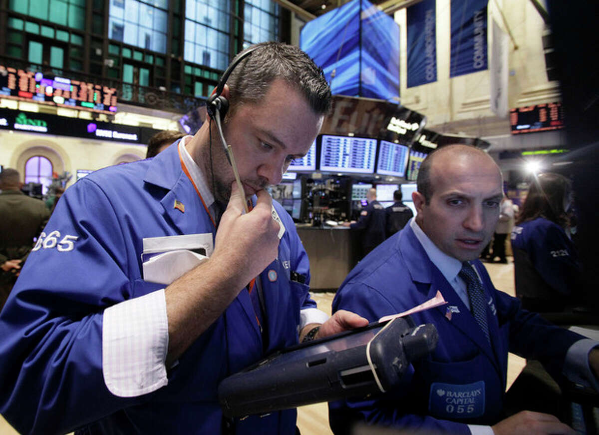 Specialist James Denaro, right, works at his post on the floor of the New York Stock Exchange Monday, Oct. 24, 2011. (AP Photo/Richard Drew)