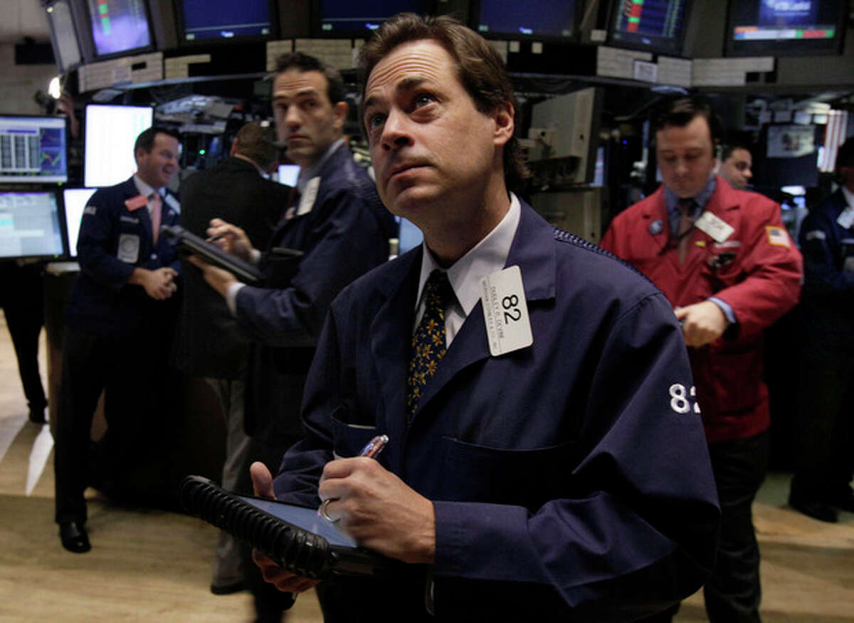 Trader Dudley Devine, center, works on the floor of the New York Stock Exchange Monday, Oct. 24, 2011. (AP Photo/Richard Drew)